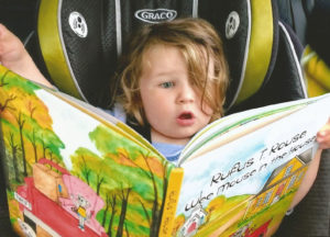 Baby in the back seat reading